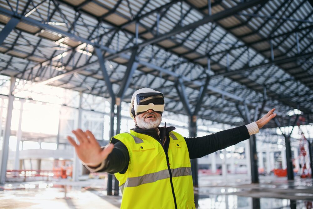 Man engineer using VR goggles on construction site